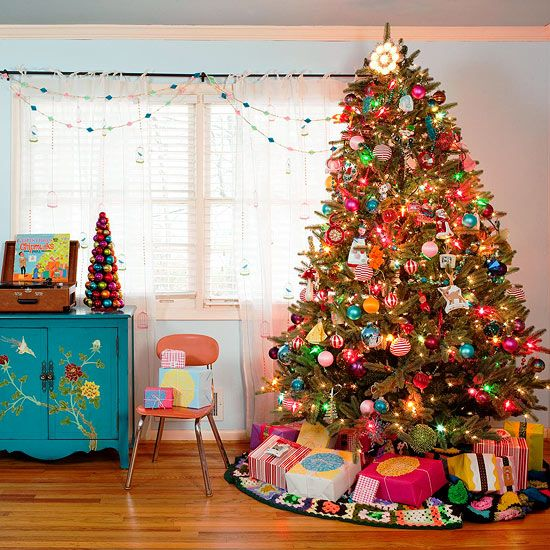 "Go with Bright Colors Give traditional colors a break and use the rainbow to inspire your Christmas decorations. Bright blue, pink, green, and gold ornaments hang from this twinkling evergreen, giving new meaning to the term ""merry and bright."" Wrap presents in brightly colored wrapping paper and hang a colorful beaded garland from the windows to round out the eclectic decorating scheme.:"