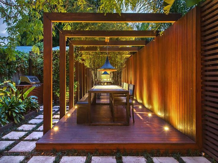 Modern take on the classic arbor. outdoor dining, outdoor lighting, patio, bench, chairs.