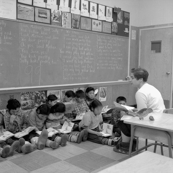Miss Velma MacDonald teaching English to Indian and Eskimo [First Nation and Inuit] children, Inuvik, N.W.T., Dec. 1959  (item 1)