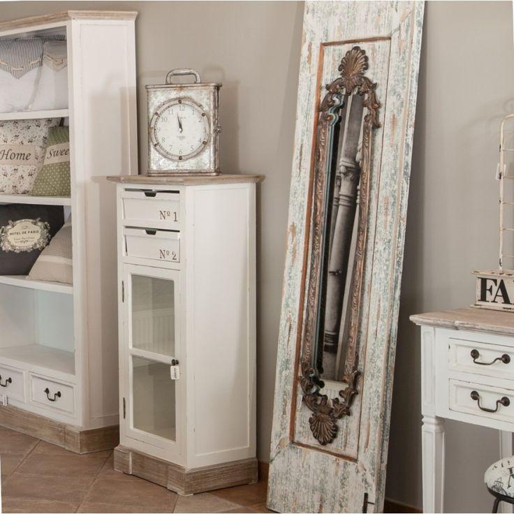 Prowansalska szafka Palida Aluro, w kolorze białym z brązowym blatem, posiada półkę za przeszklonymi drzwiczkami oraz dwie szufladki oryginalnie zrobione z drewnianych koszyczków.