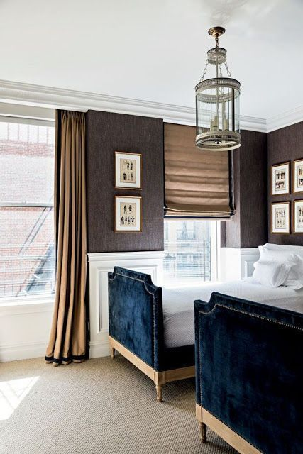 Kids Decorating Ideas. Chic, elegant boy's bedroom features a round lantern illuminating upper walls clad in brown textured wallpaper and lower walls clad in wainscoting lined with a pair of matching royal blue velvet French beds with silver nailhead trim dressed in white bedding. | Jorge Elias Retirement Home in New York Featured in Casa Vogue