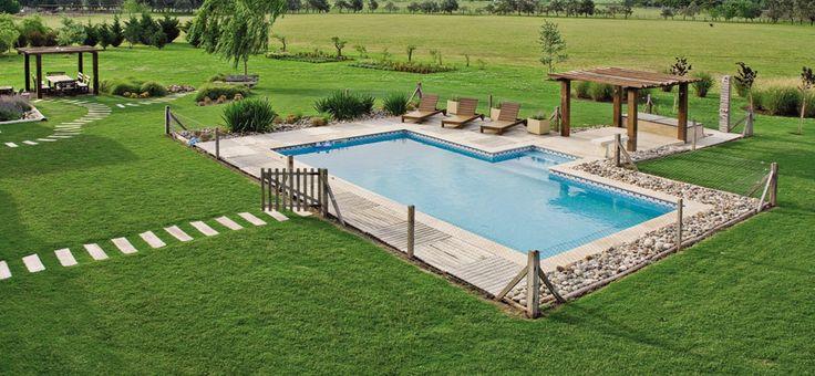 La piscina tiene un cerco de poste y alambre y un borde con planchas de deck y áreas de piedra bola. Todo suma al juego de texturas.