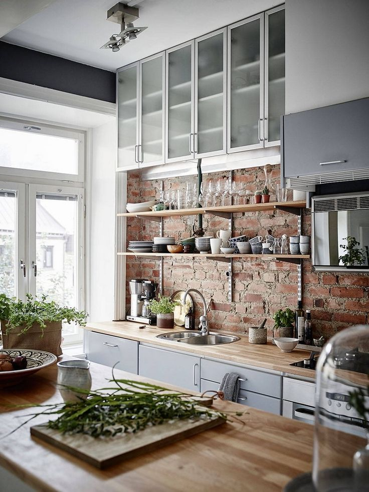 LOVE The Exposed Brick, Wood Counters, Open Shelves, Greenery.