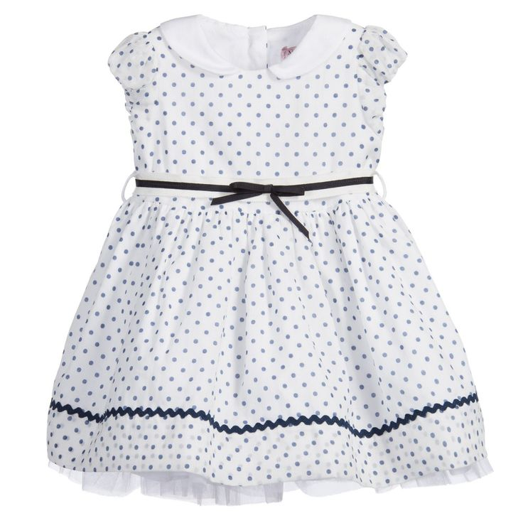 White, puff-sleeved, cotton dress by Monnalisa Bebé with all-over navy blue polka dots and a pretty, round, white satin feel collar. This fully-lined dress has a navy blue and white grosgrain tie belt with a bow and the skirt has a navy blue zigzag trim. The skirt is beautifully full with a cotton frill and tulle layer under. The dress closes with a button fastener at the back.