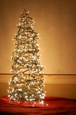 tomato cage wrapped in lights equals a really cute Christmas tree-This would be cute and easy for outside!