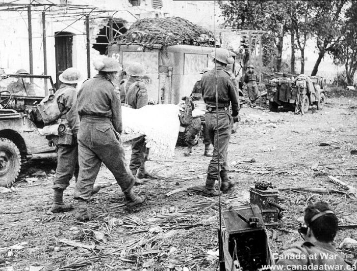 Italy (Misc.) - Although Canadian casualties were compartively light in the initial advance into Italy, they did occur. Here comrades carry a wounded soldier back on a stretcher.