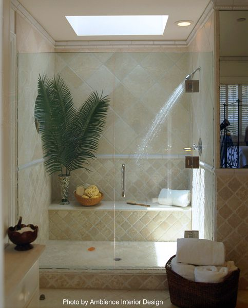 Tropical bathroom with a shower bench, recessed lighting, greenery and frameless shower doors. #tropical #vacation