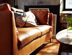 Soggiorno con divano a tre posti in pelle marrone chiaro.