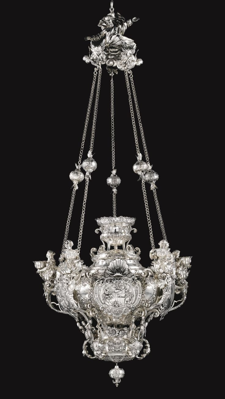 An impressive Bohemian five-light silver chandelier, Michael Josef Coscell,  1723 | of baluster form, in several sections, all richly embossed, chased and engraved with Baroque ornament including husked garlands, lambrequins and scale-work on a matted ground, further embellished with bolted silver sheet decoration in form of leaves and floral garlands | Sotheby's