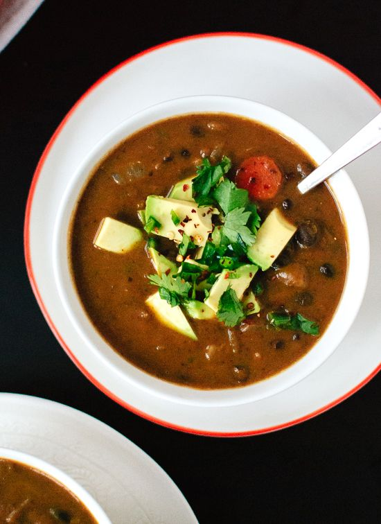 Spicy vegan black bean soup recipe - 2T olive oil; 2 yellow onions, 3 celery ribs, 1 carrot, 6 garlic cloves, cumin, red pepper flakes, 4 cans of blk beans, veg broth, cilantro, lime juice, pepper, avocado