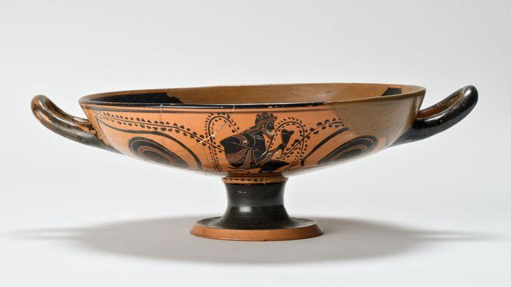 Kylix attica; fine VI secolo a.C., Periodo arcaico; ceramica dipinta a figure nere; Museo civico Goffredo Bellini, Asola, provincia di Mantova, Italia. L'immagine esterna raffigura il dio Dioniso e, nell'interno della vasca, il Gorgoneion. La kylix era una coppa per il vino. Veniva anche impiegata per il gioco del còttamos, che si svolgeva generalmente nella fase conclusiva dei banchetti.