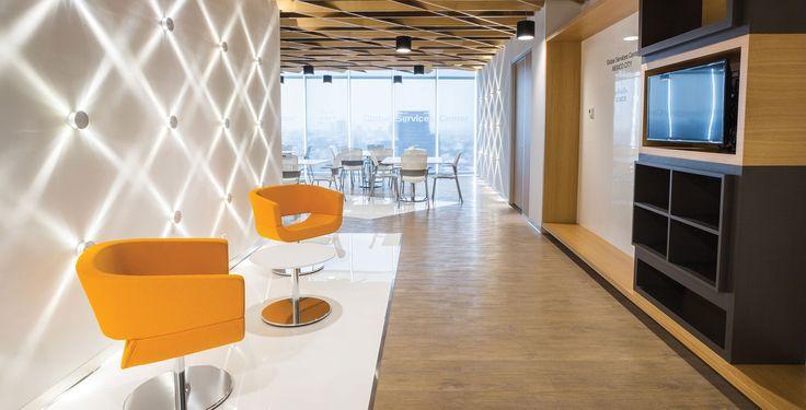 CISCO Diseño de interior, muro blanco, muro de rombos e iluminación. Plafón de rombos. Silla color naranja.