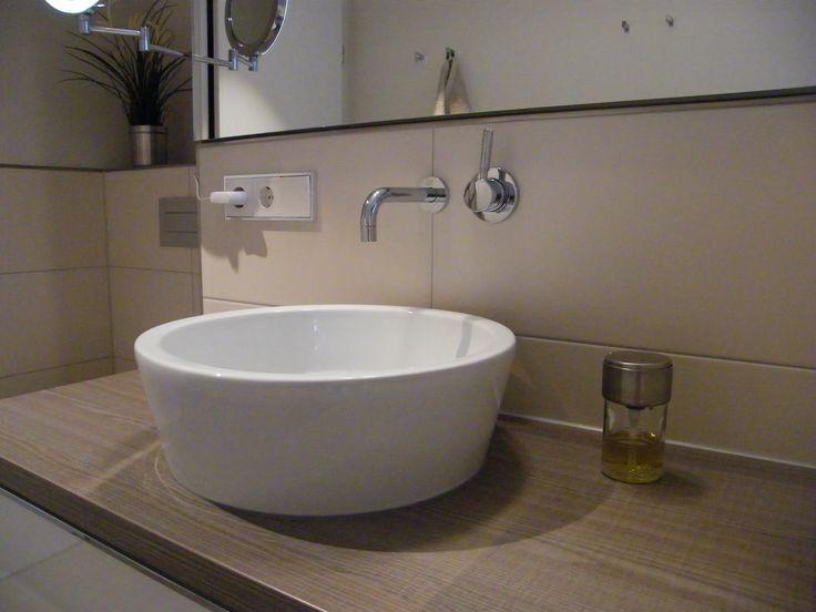 Das runde Aufsatzbecken kommt auf der braunen Waschtischplatte besonders gut zur Geltung