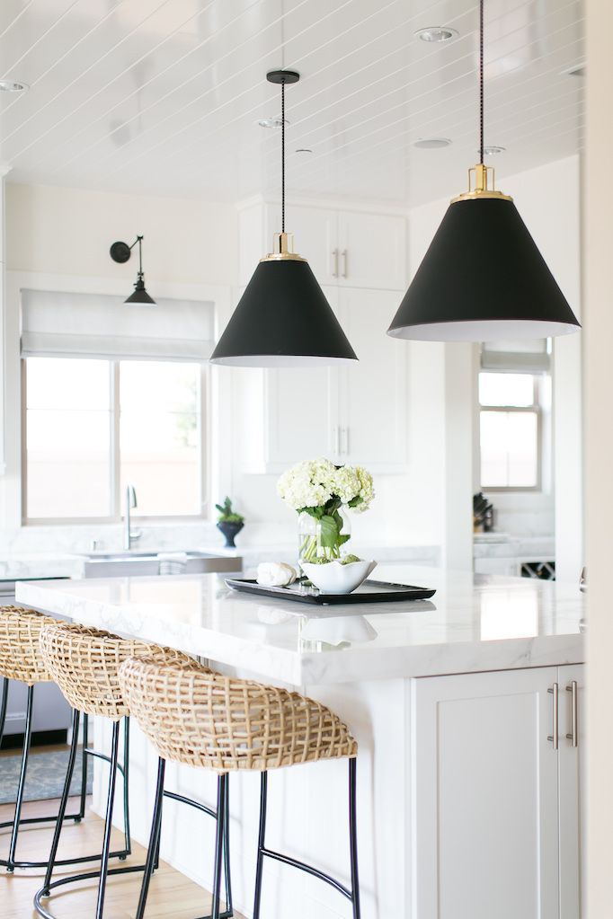 BECKI OWENS- Estillo Project: Classic Modern Kitchen. A white kitchen with statuary marble, Benjamin Moore Swiss Coffee paint, Rejuvenation swing arm sconce and black Butte cone pendants, Palecek rattan counter stools, island prep sink, and stainless steel apron sink.