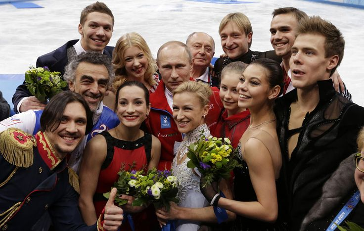 Russian President Vladimir Putin, center, poses for a photograph with the Russian team after they placed first in the team figure skating competition at the Iceberg Skating Palace, on February 9, 2014. (AP Photo/David J. Phillip)