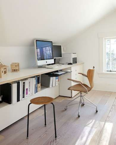 Need space for a home office? Look to your attic. These homeowners made great use of the space under the sloping ceiling with a long, low desk that includes shelving underneath. Clean lines, simple stripped flooring, and white walls and furniture make this space bright and cheerful.