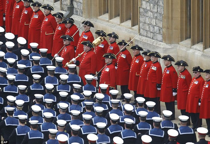 Old soldiers in the red uniforms of the Chelsea Pensioners stand to attention as sailors from the Royal Navy parade by them.