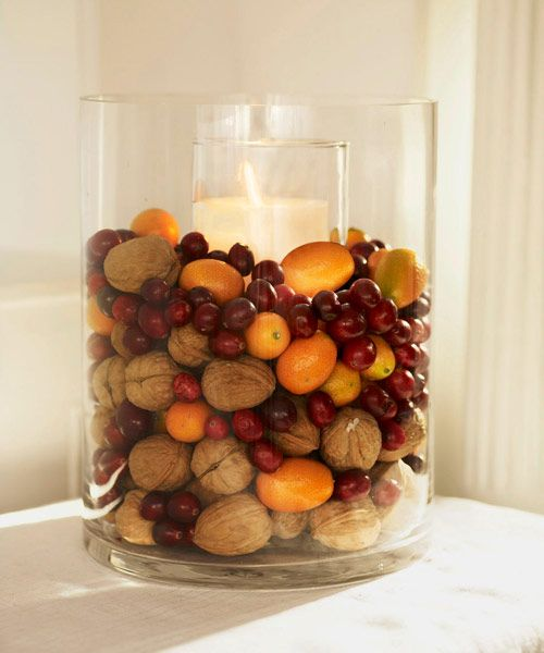 Heaped with walnuts, cranberries, and kumquats, a cylinder vase displays festive flavors. Place a tall (8- to 12-inch) pillar candle and holder inside the vase; surround with fruits and nuts. - GoodHousekeeping.com:
