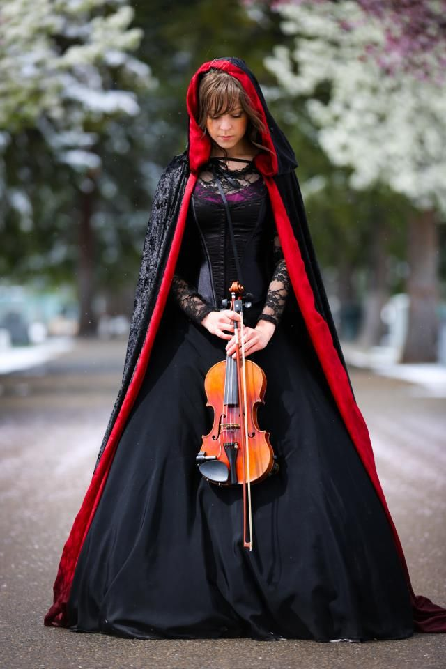 she´s Lindsey Stirling -amazing beautiful costumes and AMAZING musical talent! love her stuff http://lindseystirlingviolin.com/