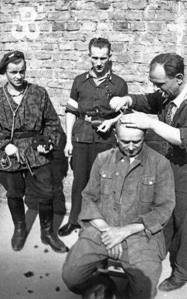 Fotografia z Powstania Warszawskiego. Strzyżenie jeńca niemieckiego na dziedzińcu gmachu PKO w asyście pilnujących go powstańców