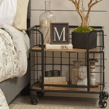 A true statement-maker, this multifunctional bar cart works overtime to combine form and function. Its metal frame is finished in black and complemented by two solid-wood shelves in a rustic oak finish. Working casters ensure it's easy to move the party. This versatile piece works in any room of the home – just roll it on over!
