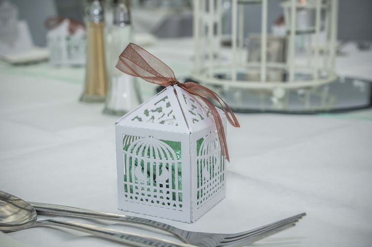 White bird cage type of box filled with sweets, could put a smile on your Special Day's guests',