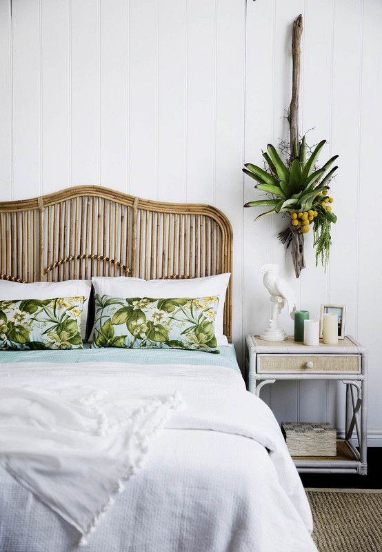 rattan headboard and vibrant florals in a breezy bedroom