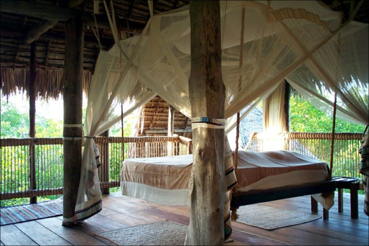 A swinging bed with curtains in an open air tree house... oh boy!