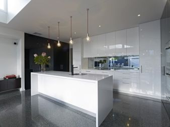 A large white kitchen on a glossy stone floor makes for an excellent entertaining space