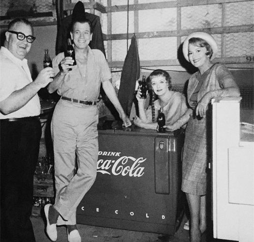 """During early production on ""Hush, Hush Sweet Charlotte"" Joan Crawford, then starring in the film, had Pepsi Cola machines on set in various locations. After her departure, a Coca-Cola machine was installed, and here Bette Davis, Olivia de Havilland, and crew pose with it."""