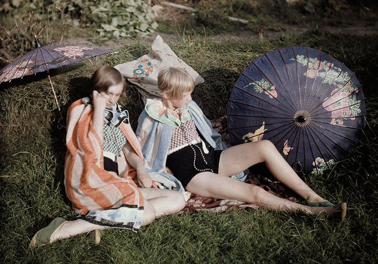 Two young girls enjoy the sun relaxing in their suits and wraps in England, September 1929.Photograph by Bernard Wakeman, National Geographi...