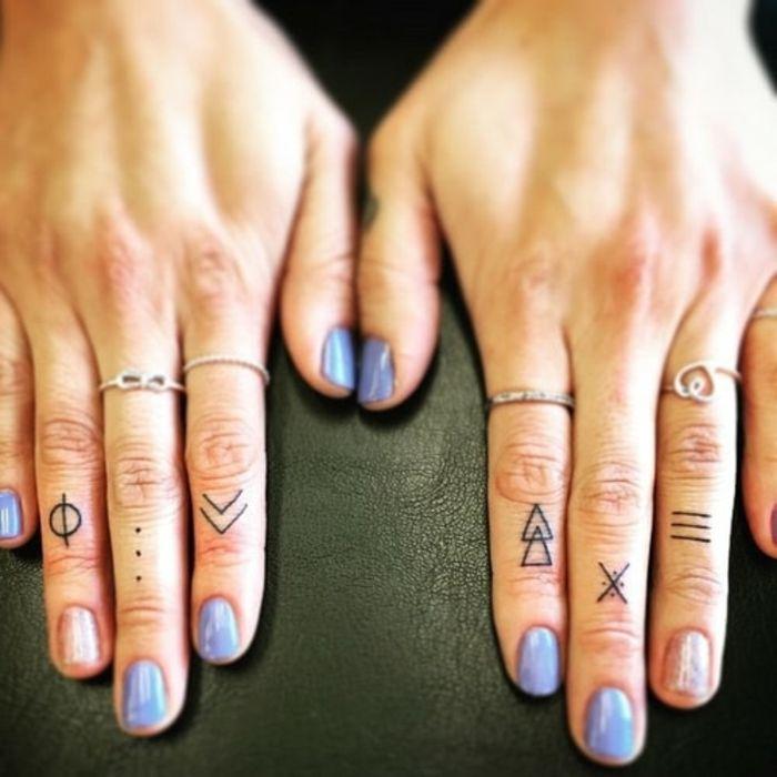 tatuaje corazon, manos de mujer con uñas de color y anillos, tatuajes minimalista con figuras geométricas en los dedos