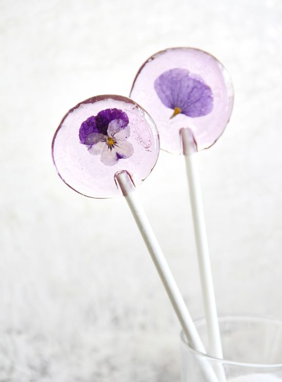 Spring Flower Lollipops   2 cups sugar  2/3 cup corn syrup  2/3 cup water  1 dram bottle candy flavoring oil (such as LorAnn, I used Blackberry)  Violet gel food coloring   10 organic whole voila flower heads or pansy petals, washed and patted dry  10 lollipop sticks