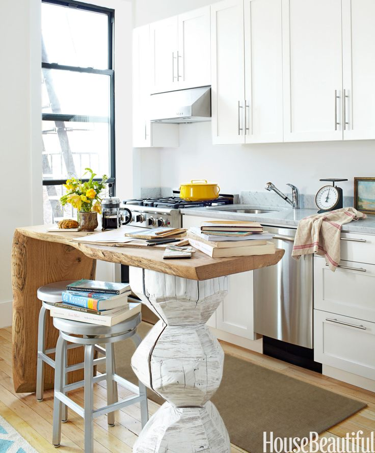 Brancusi would have liked this island, made from fallen oak and a hand-carved cherry log painted white. The honed Carrara marble counter is fitted with a 23 ¾-inch D-shaped undermount sink from Kingston Brass. A one-handled faucet by Elements of Design takes up less space and incorporates a pull-out spray. GE's 18-inch Profile dishwasher is adjacent. Walls are painted Benjamin Moore's Super White.   - HouseBeautiful.com