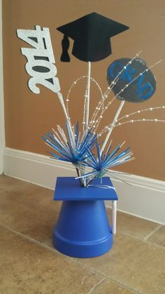 Centerpieces! All from Hobby Lobby- clay pot, wooden board (have to drill hole in center), styrofoam ball underneather to hold picks. tassel glued thru hole.  Double sided cutouts with wire between and wrap wire with floral tape around longer stick.