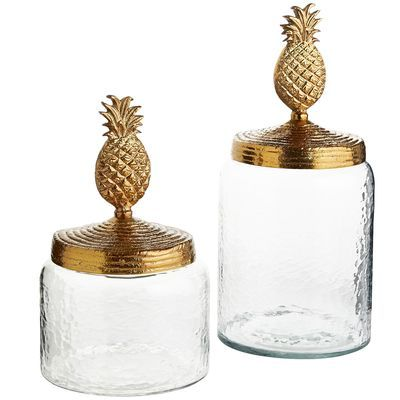 "From the Tupi word nanas, meaning ""excellent fruit,"" pineapples were once considered a symbol of wealth and were often displayed at dinner parties rather than eaten. Bring home tradition with our beautiful canisters, handcrafted of hammered glass with a golden lacquered pineapple top. A wealth of style, you might say."
