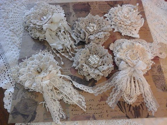 Six shabby and vintage handmade flowers. Two are made with doilies. Four are with pieces of shabby scraps. Beige and white. Handmade bling in the center. These are made to be added to projects or whatever.