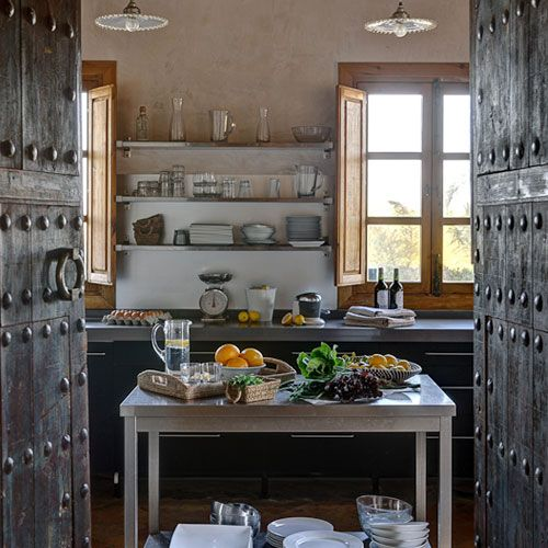 Heavy wooden doors open into the charming kitchen at Casa La Siesta, a converted farmhouse in Andalucia, Spain. #travel