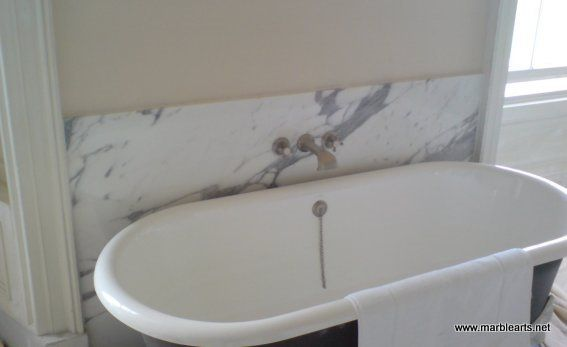 A simple marble bath splash back panel for a free standing bath