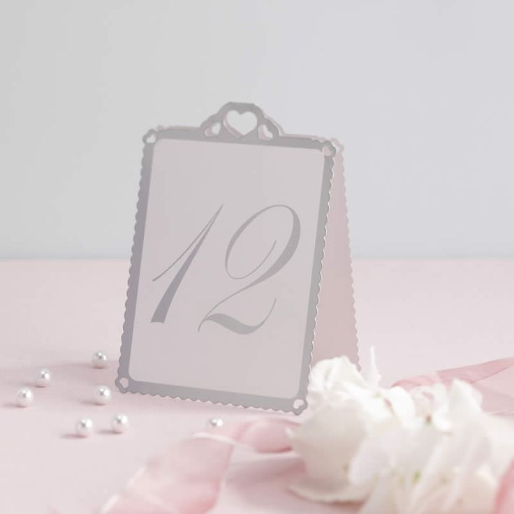 Decorative table number cards with lasercut heart design and silver border. The numbers 1 to 12 are printed in silver in large easy to read print on both sides of the card. These table number cards can stand alone or in a holder. Set of 12 tent style table numbers.