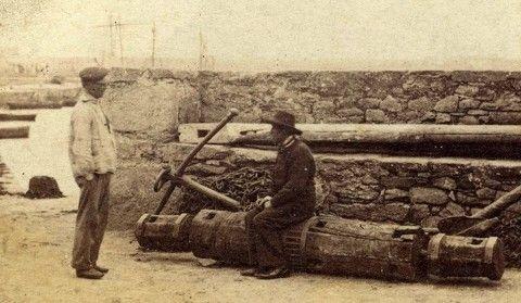 Deux marins discutent près du mur de la base du quai, l'un est assis sur un antique guindeau à barres comme le montre les trous carrés. 1857, Roscoff,  Brittany