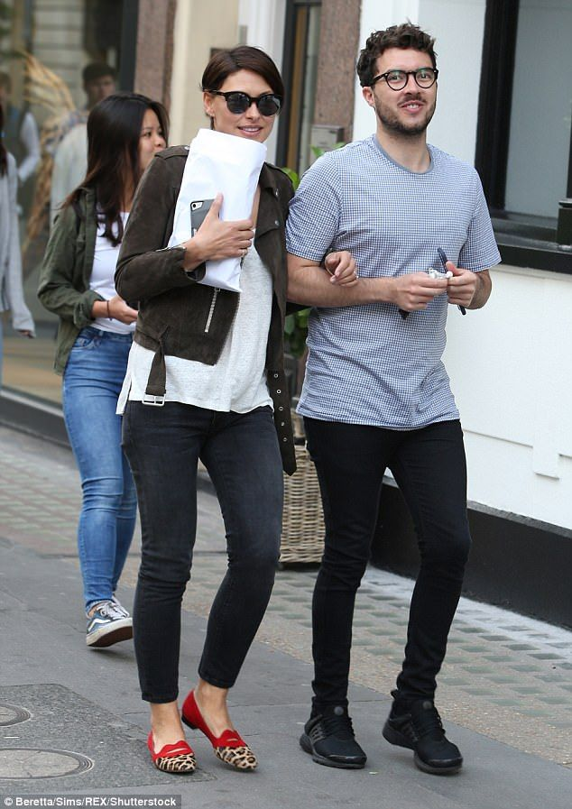 Trendy: Ambling on the street arm in arm with a male pal, the Big Brother presenter looked...