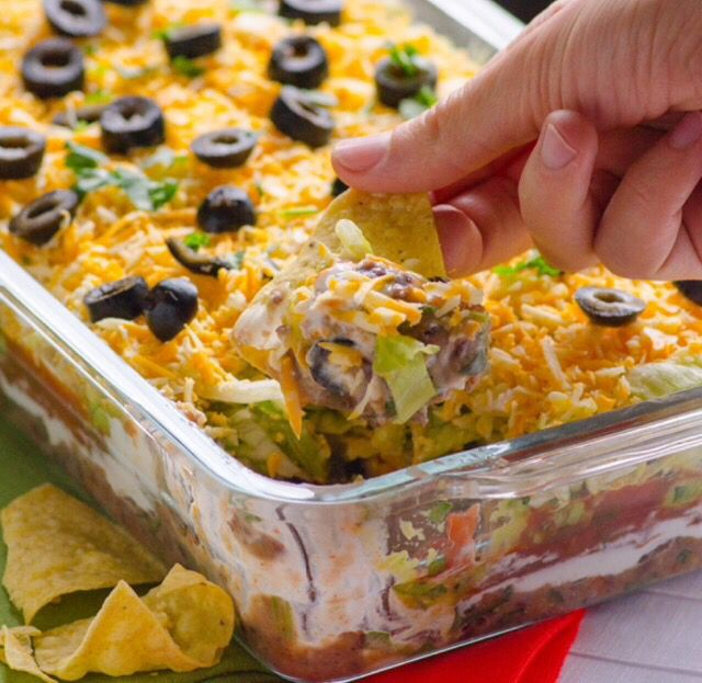7 Layer Taco Dip: refried beans, taco meat, sour cream, shredded lettuce, shredded cheese, diced tomatoes, & chopped black olives. Serve chilled with tortilla chips!