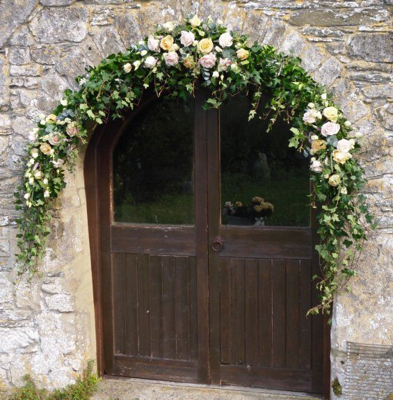 Flower arch using lots of ivy and clusters of flowers for impact rather than all the way round. Could use flowers in any colour mix.