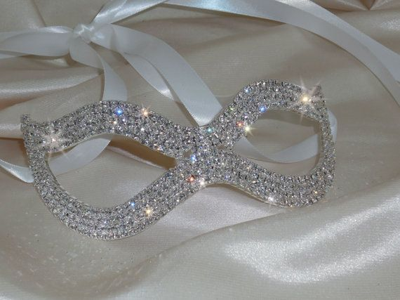 ...This Beautiful Silver Rhinestone Bridal Mask is adorned with a satin ribbons on both ends for easy adjustment...Rhinestone mask measures approximate 6 W & 2 1/2L...With satin ribbon on both sides...  Comes available in additional colors as well...Ivory, Black and Light Silver...choose during checkout...White is standard  Matching Headband, Earring and Bracelet sold separately…