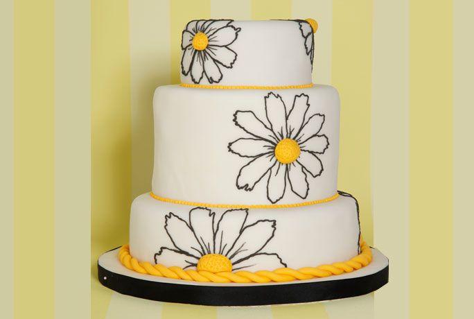 Diferentes alturas en tres pisos de torta galesa y torta de chocolate negro con ganache de chocolate blanco y almendras caramelizadas. Cubierta de pasta de almendras y enormes margaritas dibujada