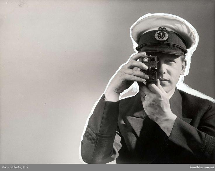 Reklam för filmkamera, ca 1940-1949. Man iklädd skepparhatt och kavaj håller filmkamera framför ögat. Retuscherad bild. Foto: Erik Holmén för Nordiska Kompaniet