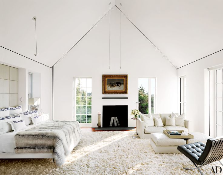 A white master bedroom in a Natntucket home designed be Jacobsen Architecture.