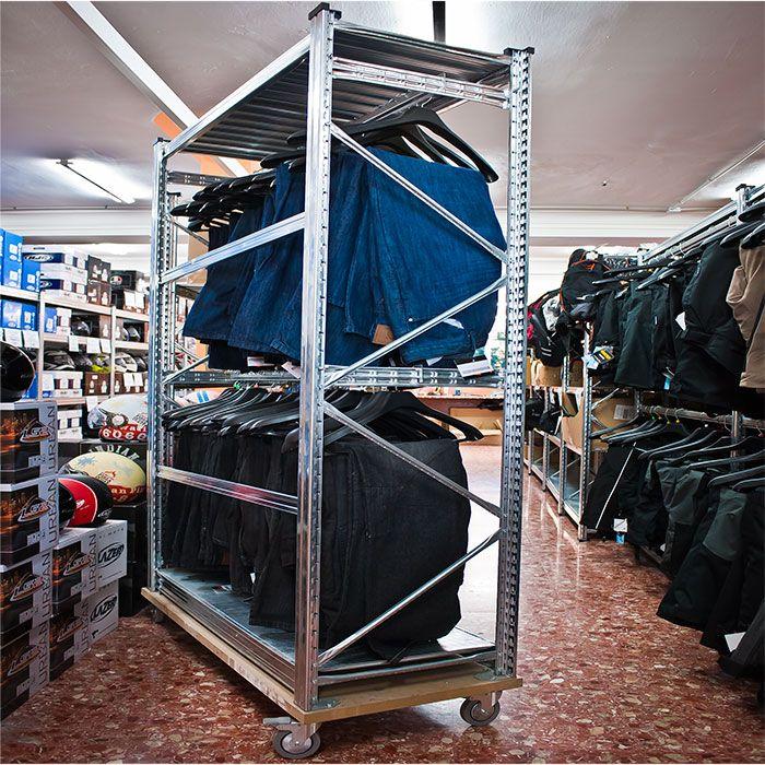 Estanterías metálicas con base con ruedas para almacenaje y exposición de textiles. Con estantes metálicos lisos y barras colgadoras. https://www.esmelux.com/galeria-de-estanter%C3%ADas-para-textil