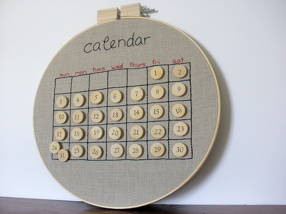 a embroidered calendar on raw linen in a wooden embroidery hoop. the dates are (re)movable wood tokens.
